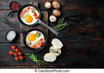 Fried eggs with cherry tomatoe and bread for breakfast in cast iron frying pan, on old dark wooden table background, top view flat lay , with space for text copyspace