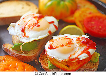Fried eggs with chili sauce on avocado toast