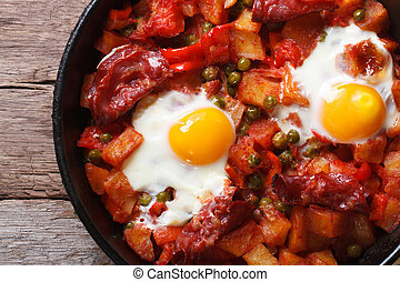 Fried eggs with chorizo in the pan close up. horizontal top...