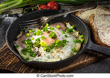 Fried eggs with ham on an old wooden background.