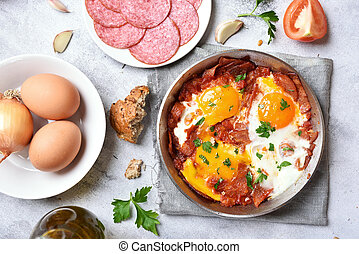 Fried eggs with salami, bacon and tomatoes