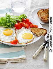 Fried Eggs with tomato, lettuce and bread on a white plate