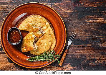 Fried empanadas with minced beef meat served on a plate with chili sauce. Dark Wooden background. Top view. Copy space