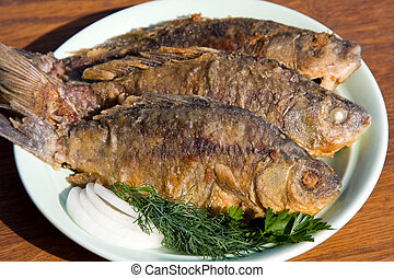 Fried fish crucian in plate on wooden table