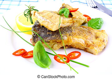 Fried fish fillets with lemon, chili peppers slice on white plate