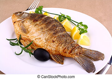 Fried fish on white plate with lemon, fork and knife