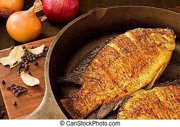 Fried fish (tilapia) on a pan, scatterd peppercorns, bay...