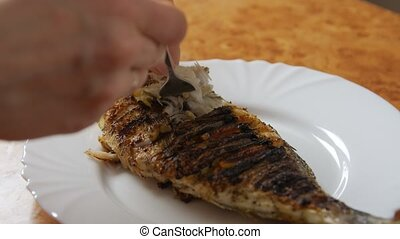 Fried fish tasting grilled Dorado woman hands closeup hot steam