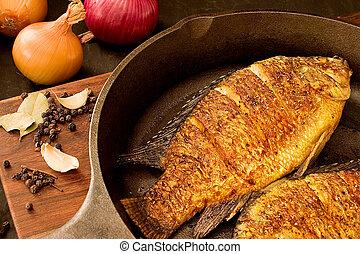 Fried fish (tilapia) on a pan, scatterd peppercorns, bay...