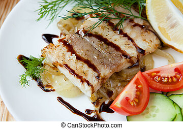 Fried fish with vegetables and sauce, food close up