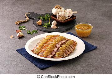 Fried garlic pork feet on white plate with herbs