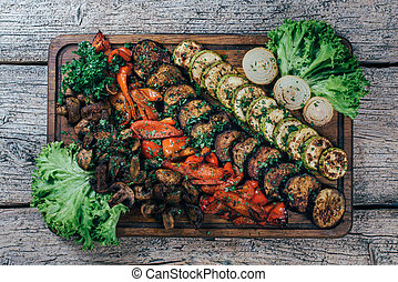 Fried grilled vegetables appetizing on a wooden board, along with leaves of green salad