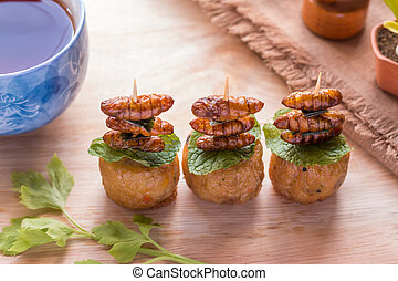 Fried insects - Wood worm insect crispy with chicken roll after fried and add a light coating of sauce and garnish Thai pepper powder and tea on wooden background, Select focus