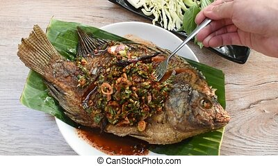 fried mango fish dressing spicy sauce stabbing by silver ...