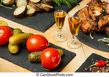 Fried meat, potatoes, vegetables on black slate plates and...