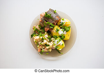 Fried meat with potato salad, greens seasoning white sauce, on a white plate. Clipping path.