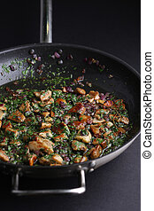 Fried mushrooms with onions and greens in a skillet on dark background