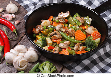 fried mushrooms with vegetables in a frying pan