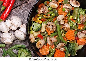 fried mushrooms with vegetables in a pan top view
