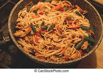 Fried noodles with vegetables and turkey meat in a black iron wok pan on