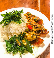 Fried one-thousand-year egg with crispy holy basil leaves and rice dish on a wood table, Spicy popular traditional thai authentic signature menu for lunch or dinner meal on comfort Thai street food stalls.