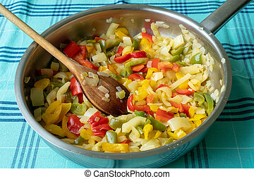 Fried pepper on a frying pan. Fried colorful vegetables on a frying pan.