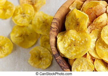 Fried plantain chips in a wooden bowl.