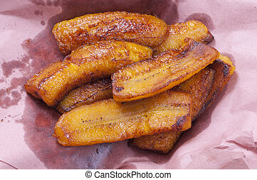 Sliced greasy fried plantain bananas on pink paper to soak up excess grease