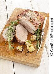 fried pork roast on a wooden board