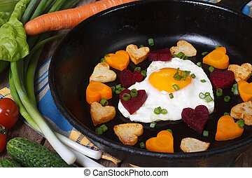 Fried potatoes, carrots, beets and egg in a heart shape