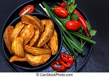 Fried potatoes on a black wooden plate with fresh vegetables - onions, tomatoes, parsley. Black background