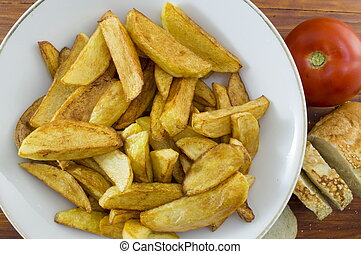 Fried potatoes on a plate decorated with sliced bread and a tomato