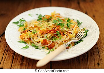 Fried potatoes on white plate with fork