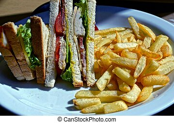 fried potatoes with a sandwich on a white plate