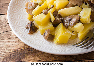 Fried potatoes with mushrooms and onions. Wooden table
