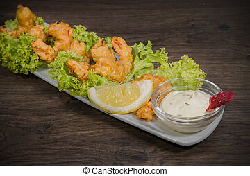 Fried prawns on a plate with sauce and on a wooden background