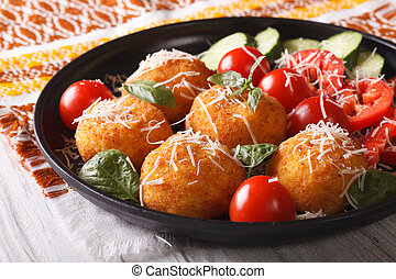 Fried rice balls and fresh vegetable salad on a plate. horizontal