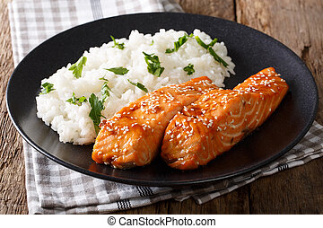 Fried salmon in a honey-soy glaze and rice close-up. ...