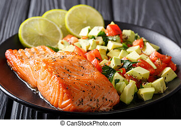 Fried salmon steak with avocado tomato salsa closeup. horizontal