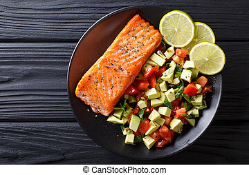 Fried salmon steak with avocado tomato salsa closeup. Horizontal top view