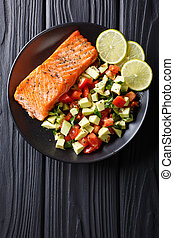 Fried salmon steak with avocado tomato salsa closeup. Vertical top view