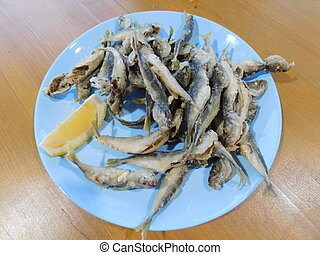 fried sardines with lemon on a plate
