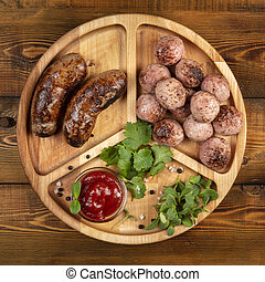 Fried sausages and meat balls with sauce and herbs on a wooden plate. Top.