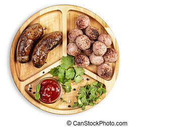 Fried sausages and meat balls with sauce and herbs on a wooden plate. White background. Top.