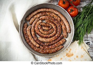 fried sausages on a frying pan on a wooden background. selective focus