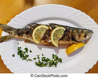 fried sea bass with lemon slices on a plate