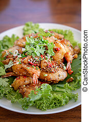 Fried Seafood shrimp prawn fish mussel squid fish on the salad vegetagle in white circle dish on wood table.
