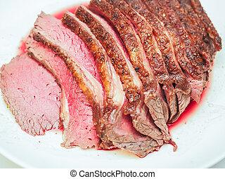 Fried seasoned juicy red meat on white plate