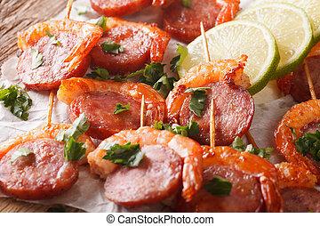 Fried shrimp and chorizo on skewers close-up. horizontal