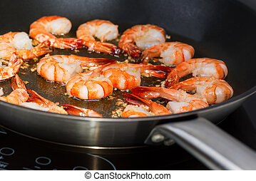 Fried shrimp in skillet - Chinese cooking: Shrimp in wok on...